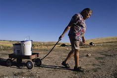 Pine Ridge Indian Reservation, South Dakota, USA --- A native American woman hikes to a roadside tank to fetch water