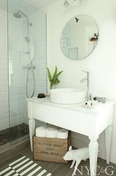 The vanity in the master bath is made from a vintage table topped with Carrara marble. The sink and faucet are from Kraus, and the shower fittings are from Hansgrohe.