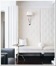I love this living area - this would also be a great dining nook, gorgeous tufted buttons, and great use of height. Love the lamp too - Stunning!