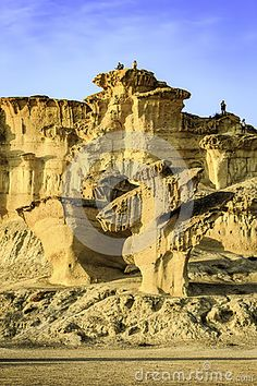 People stood on the top of natural sandstone sculptures in Bolnuevo, Murcia, Spain.