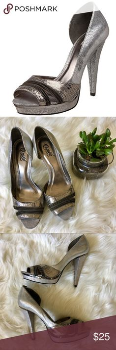 """Carlos Santana Zapato Pewter/Black Pump Heel Carlos Santana Zapato in Pewter Leather. Leather upper in a dress platform pump style with a round open toe. Features zipper embellishment at vamp, open inner arches. Smooth lining & cushioned insole. 1/2"""" platform, 4"""" heel. ✨ Asymmetrical pump. Its open toe & open inner arch showcase your foot in flirty fashion, with a fun zipper embellishment & spike heel adding a hint of playful drama. A way to supercharge your workday attire, it's also ideal…"""