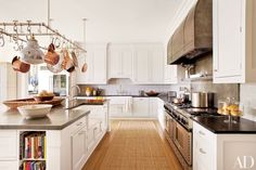 A bespoke Ann-Morris pot-rack light fixture is suspended in the kitchen of a chic Hamptons retreat decorated by Carrier and Co.; the backsplash tiles are by Country Floors, and the double range is by BlueStar. The space is proof that you can't go wrong with white cabinets.