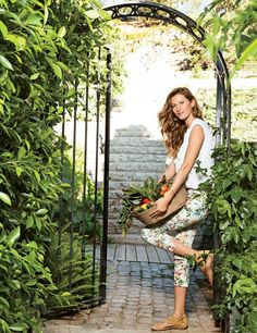 Model Gisele Bündchen collects produce from the garden at the Los Angeles home she shares with NFL quarterback Tom Brady and their children. The architecture is by Landry Design Group, and Joan Behnke & Assoc. oversaw the interiors; the landscape design is by the late Dennis Hickok. For details see Sources.