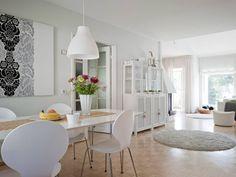 Keittiöstä näkyy koko yläkerta. Pitkä ruokapöytä ja tuolit ovat Iskusta ja valaisin on Ikeasta. Seinällä on Sarin Marimekon Ananas-kankaasta teettämä taulu.