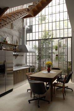 factory-metal-windows-garden-estudio-vitorpenha-gardenista. Two-story factory windows and French doors bring sunlight into a kitchen by Brazil-based Estudio Vitor Penha. WOW!!!
