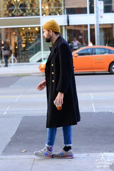 Mustard beanie, black overcoat, jeans and trainers.
