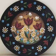 A wood plate has been hand painted with my primitive folk art design. The plate, which measures 9 1/2 inches in diameter, is a primitive style floral painting with tulips, daisies, blue spring flowers and buzzing bees. It has been sealed with matte finish. PLEASE NOTE: THIS ITEM IS MADE TO ORDER: Each plate is individually hand painted and the one you receive may vary slightly from the one pictured. The plate will be painted and shipped within three weeks of the date it was ordered. I...