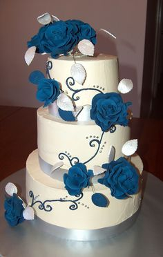 pinner said: My first wedding cake.  I was so pleased with how it turned out.  The cake details.  Bottom tier is chocolate cake, middle tier is vanilla cake, top tier is chocolate cake.  It has all been filled and frosted in buttercream.  The blue roses I made myself for the first time in this manner by watching Edna's tutorial at designmeacake.com.  The blue roses were to match the bridesmaides blue dresses.  The silver ribbon at the bottom of the cakes are to match silver borders on the…