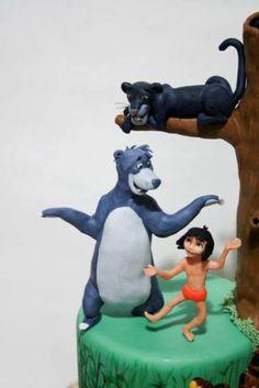 Un simpatico orsetto amico di Mowgli. Occorrente: Pasta di zucchero grigio scuro, grigio chiaro, bianca, rosa, nera Spiedino di legno Base di