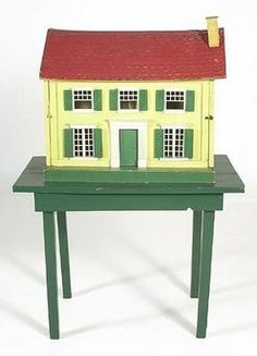 dolls, America, A Schoenhut dollhouse. In traditional Colonial style with four rooms in green, white, yellow and red. Original label.