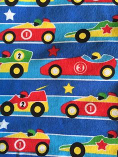 """Three piece toddler bed sheet set with race cars on blue background. Fitted sheet, pillow case measures 20"""" X 13"""", and flat top sheet, all of cotton flannel. Bright colors. Made and ready to ship. Made in a smoke free home.          The adorable model is my sweet grandson -- you have to get your own.    Toddler mattresses are the same size as crib mattresses. 
