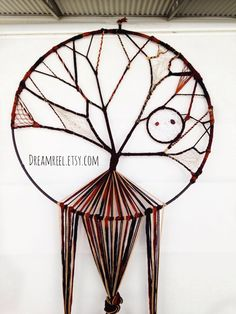 This tree of life dreamcatcher is divine in its elaborate detail. All designed and weaved by hand with patterned yarns, brown cord, ribbon, hemp.