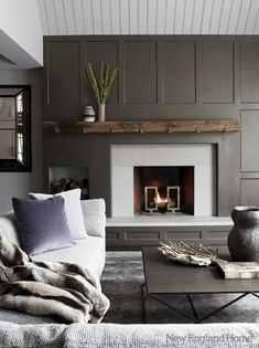 Grey Paneled walls with an old hand hewn beam as a mantle.