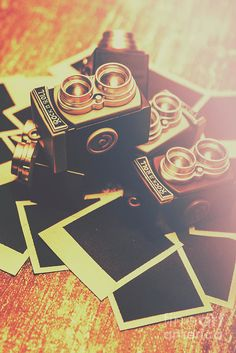Retro twin lens reflex camera toys laying in a creative still life on instant blank photos. Photography symbols by Jorgo Photography - Wall Art Gallery