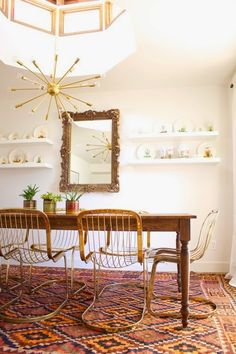 Fresh fun, mid century influenced dining room.  Gold gilded mirror juxtaposes unexpectedly between minimalist china shelves.  Beautiful brass Cidue Vicenca cantilever chairs, kilim rug, and farmhouse table.     Inspiring Spaces: The Dining Room | East to West