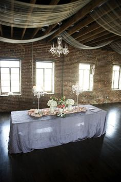 Love it all...the ceiling beams, tenting and chandelier, the stone wall, flooding sunlight, dark floors...