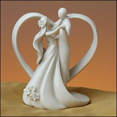 """Everlasting Love Cake Top    What a beautiful expression of love for the top of your wedding cake. The bride and groom share a romantic embrace in front of an open scrolling heart. Porcelain flowers accent the bride's veil and the edge of her dress. Made of glazed porcelain this cake topper can serve as a beautiful keepsake figurine for years to come. Measures 5.25"""" wide x 6.5"""" tall."""