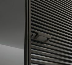 slim sliding Even door, characterized by the thin jamb. Brown aluminium structure and grey transparent glass