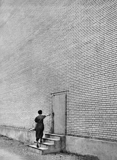 """© Fabrik, A Photo Epos of Technology by Jakob Tuggener published by Steidl The """"expressionist aesthetic of the silent movie"""" seems a good description of the work ofJakob Tuggener (1904–1988) a Swiss photographer, film maker and painter. The scale of the anonymous brick wall with its single small door dwarfing the figure eloquently describes the dehumanising character of the factory. (via Fabrik Jakob Tuggener 