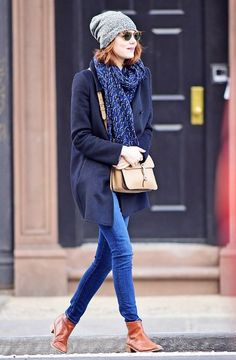 Emma Stone looks adorable in a navy coat, knit beanie and casual tan boots