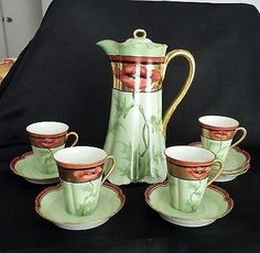 This gorgeous 9 1/2  high pot, 4 demi-cups and 6 saucers are decorated in red poppies on gold with shaded light green stems and ground. The rim, finial and handle are gilded. The cups are 3  high with