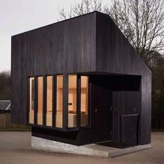 Burnt wood clads this gatehouse designed by NORD Architecture for a historic palace in southeast England  a reference to the storm that destroyed many of the estate's trees in 1987. Photograph is by Leon Chew. We're featuring some of the best wooden houses on Instagram today and there's even more examples on http://ift.tt/20VsQ41 #architecture #wood #UK by dezeen