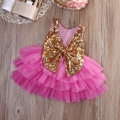 Glam Baby Love! The Brittany dress is shimmering in gold sequins and fuchsia layer tulle. Cute cutout and bow on the back.