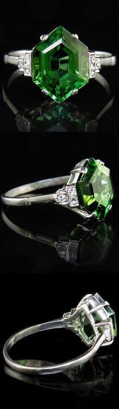 Tourmaline Ring.  Vintage 1930s tourmaline and diamond ring set with three eight cut diamonds to each shoulder. Claw set in white metal, white metal shank. Stamped PLAT. The 12.5mm long natural green tourmaline os flanked by six diamonds totalling 0.10ct. An entirely original Art Deco era ring.