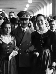 Hitler poses with two young German women for a photo. Undoubtably acting as a bragging right for them during this time period.