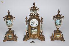 Terno com relógio e par de ânforas de metal dourado e porcelana. Alturas 33 cm (cada ânfora) e 41 cm