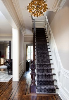 This Upper East Side Townhouse was transformed into a sophisticated space by designer Blair Harris. Check out the amazing lighting fixtures! New York Townhouse, Townhouse Interior, Brownstone Interiors, Modern Victorian, Victorian Homes, Staircase Runner, Stair Runners, Navy Stair Runner, Black Staircase