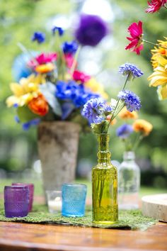 Whimsical Colored Glass Centerpiece Idea| Afloral.com Depression glass style tea light holders and vintage style glass bottle. #WeddingDesign