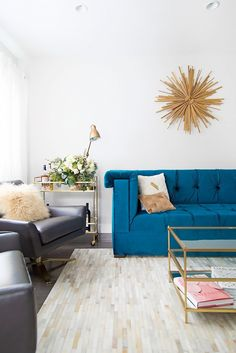 Living space with a jewel-toned velvet sofa,  leather armchairs, and a patch work rug