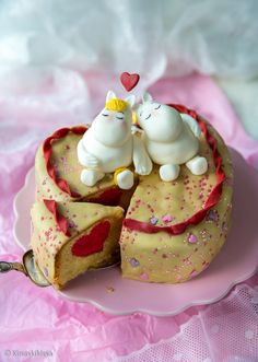 """Toisiinsa nojailevat Muumipeikko ja Niiskuneiti tähdittävät kakkua, jonka sisuskin on rakkautta täynnä! Kakku sopii esimerkiksi lastenjuhliin ja ystävänpäivään. Kuorrutteena on käytetty valkosuklaasta tehtyä suklaamassaa, jota voi halutessaan värjätä pastaväreillä tai tuunata """"makusuklailla"""". Ripottelemalla nonparellit ja koristerakeet kaulimisvaiheessa levyn pintaan, saat kakun sivureunoja myöten koristellun kuorrutteen, joka ei välttämättä kaipaa muuta koristelua. Vinkki: Käytetyn…"""