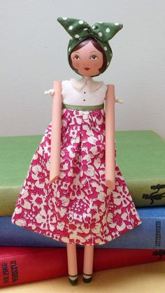 This 1940s inspired wooden art doll has been designed and lovingly hand made in Isabellas Secret Attic studio. Esmie is 16.5cm tall with a wooden head and limbs and a cloth body; she has been constructed using traditional stringing techniques to give a loose limbed effect. Her