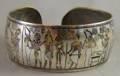 """Egyptian Revival cuff bracelet, decorated with scenes from the Burial Chamber of Tutankhamun. Silver plated, Reed & Barton """"Damascene""""."""