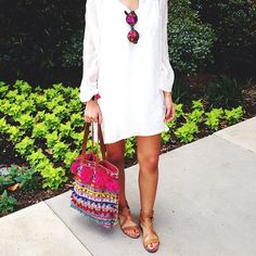 white kaftan dress, camel colored leather sandals and a multi colored tote bag
