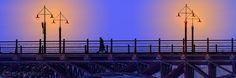 Auch hier wieder die Wirkung eines Scherenschnitts, aber sehr farbenfroh. Diesmal eine Passantin in der Morgendämmerung im Schein der Straßenlaternen auf einer Brücke. Teil der Twillight Serie.   Again, the effect of a paper cutting, but very colorful. This time a passerby at dawn in the glow of streetlights on a bridge. Part of the Twilight series.