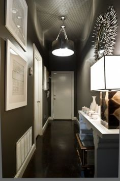 "Use wall color to create an art gallery. The palette in this stunning hallway is simple: white and deep gray-brown. The wall color acts as a perfect backdrop for all the white design elements. Simple white picture frames, white console table and a ""porcupine quill"" mirror all stand out beautifully."