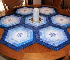 Gail of Quilt Sew Pieceful says: This beautiful winter table topper/runner will be amazing on your round table! It measures 41 1/2 inches in diameter (105 cm). You don't need to put this away after Christmas. It can be a showpiece all winter long! It features 7 hexagon shaped blocks. Each block has a different machine embroidered snowflake in blue on white in the center. Each hexagon is made up of different blue fabrics, many of which have silver highlights.