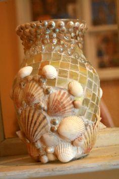 Este precioso vaso se cubre con un montón de conchas naturales, delicadas estrellas de mar, hermoso pastel y pastel amarillo mosaico en varios tonos.