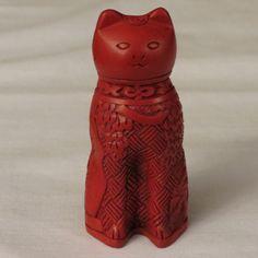 Это замысловатой резьбой кошка сделана из киновари лака, художественная форме, разработанной в Китае и достигающего своего пика популярности в 15-м веке. Процесс вовлекаются слоев древесины или конопли с сотнями слоев в киновари лаком, позволяя каждому сухой перед добавлением другого, то резьба замысловатые узоры и части.