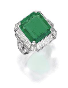 PLATINUM, EMERALD AND DIAMOND RING. Centered by an emerald-cut emerald weighing 9.48 carats, framed by tapered baguette and baguette diamonds weighing approximately 4.40 carats, size 5½; circa 1930.
