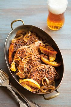 Cider-Braised Pork Chops with Apples: 1 tsp. dried oregano; 1/2 tsp. five-spice powder; 1/2 tsp. sweet paprika; Salt and freshly ground pepper; 4 thin boneless center-cut pork loin chops, about 1 lb. (500 g.) total; 4 tsp. canola oil; 1 yellow onion, thinly sliced;  1/3 cup (3 fl. oz./80 ml.) apple cider; 2 Tbs. red wine vinegar; 1 Fuji apple, peeled, halved, cored and cut into 8 wedges; 1 cup (8 fl. oz./250 ml.) chicken broth; 1/4 cup (2 fl. oz./60 ml.) evaporated milk.