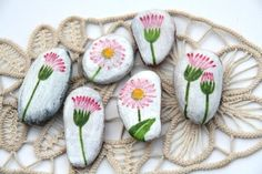 Pink flowers, green stems, painted on almost white rocks. DO.