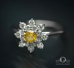 """""""AND IT WAS YELLOW"""" Yellow Diamonds are more rare and expensive than white diamonds. The fire and color of the center stone mounted in a Snow Flake setting Makes this piece unique in it's kind. Perfect for an Engagement or anyversary.  Center .22ct fancy vivid yellow I1 mount .40ct G - VS in 18kt white gold"""