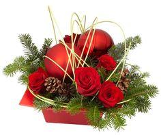 Une coupe florale pour Noël rouge passion avec des pommes de pin, du sapin et des roses. Une création Oasis.