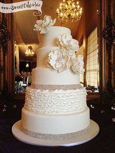 Ruffles and Crystals Wedding Cake 5 tier white fondant wedding cake with a single tier of ruffles and rhinestone ribbon borders and hand made sugar flowers with crystal centers.