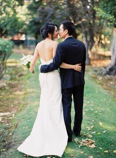 Bride and groom walking and kissing, shot from behind-- cute!