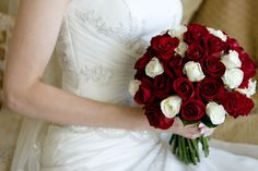 Posy shape bouquets of Magnum Red and Bianca White Roses with a camellia leaf collar
